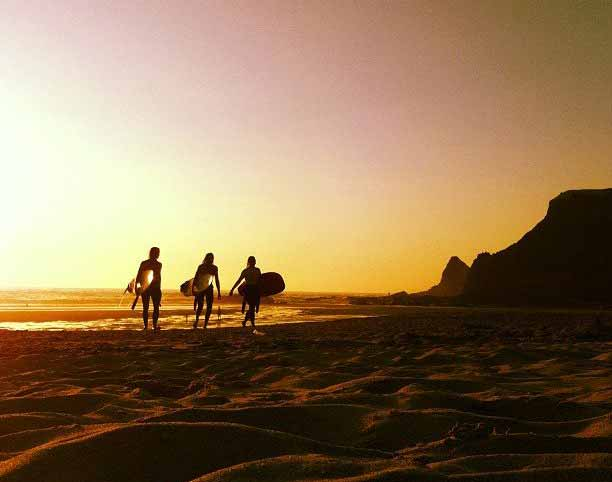 Odeceixe surf sunset surfers walking along the beach at sunset